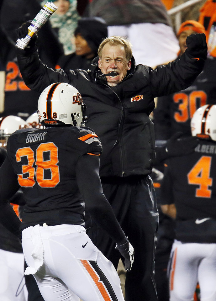 Glenn Spencer, OSU defensive coordinator, reacts as his defense, including Emmanuel Ogbah (38), leaves the field after a stop on third down in the fourth quarter during a college football game between the Oklahoma State University Cowboys (OSU) and the Baylor University Bears (BU) at Boone Pickens Stadium in Stillwater, Okla., Saturday, Nov. 23, 2013. OSU won, 49-17. Photo by Nate Billings, The Oklahoman