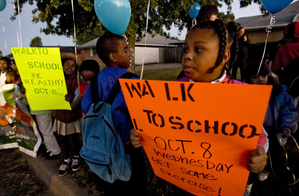 Photo - Janesha Roberson holds a sign as she and other students of Western Village Academy prepare to participate in the International Walk to School Day on Wednesday, Oct. 8, 2008, in Oklahoma City, Okla.  CHRIS LANDSBERGER, THE OKLAHOMAN  ORG XMIT: KOD