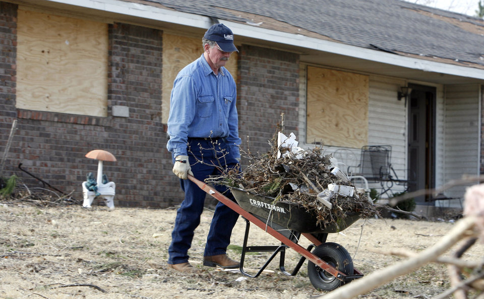 Photo - Mike Rolen cleans up tornado damage in the Majestic Hills neighborhood north of Ardmore, Thursday, Feb. 12, 2009, PHOTO BY SARAH PHIPPS, THE OKLAHOMAN