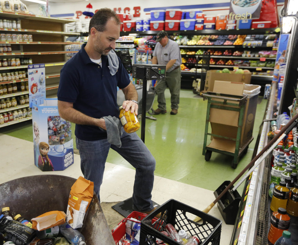 "Photo - Bud Richards, produce manager at ""White's Foodliner"" cleans up floors and items in the store after an early morning 5.6 magnitude earthquake struck Pawnee, Okla. Saturday, Sept. 3, 2016.  Photo by Paul Hellstern, The Oklahoman"