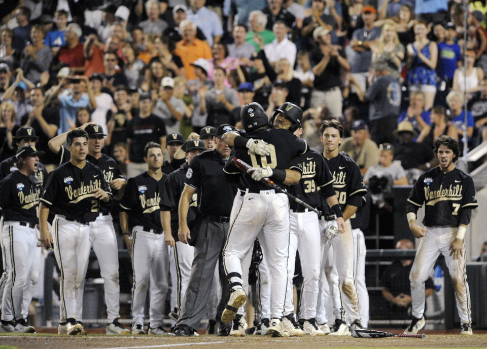 Photo - Vanderbilt's John Norwood (10) celebrates with his teammates after hitting a home run against Virginia in the eighth inning of Game 3 of the best-of-three NCAA baseball College World Series finals in Omaha, Neb., Wednesday, June 25, 2014. (AP Photo/Eric Francis)