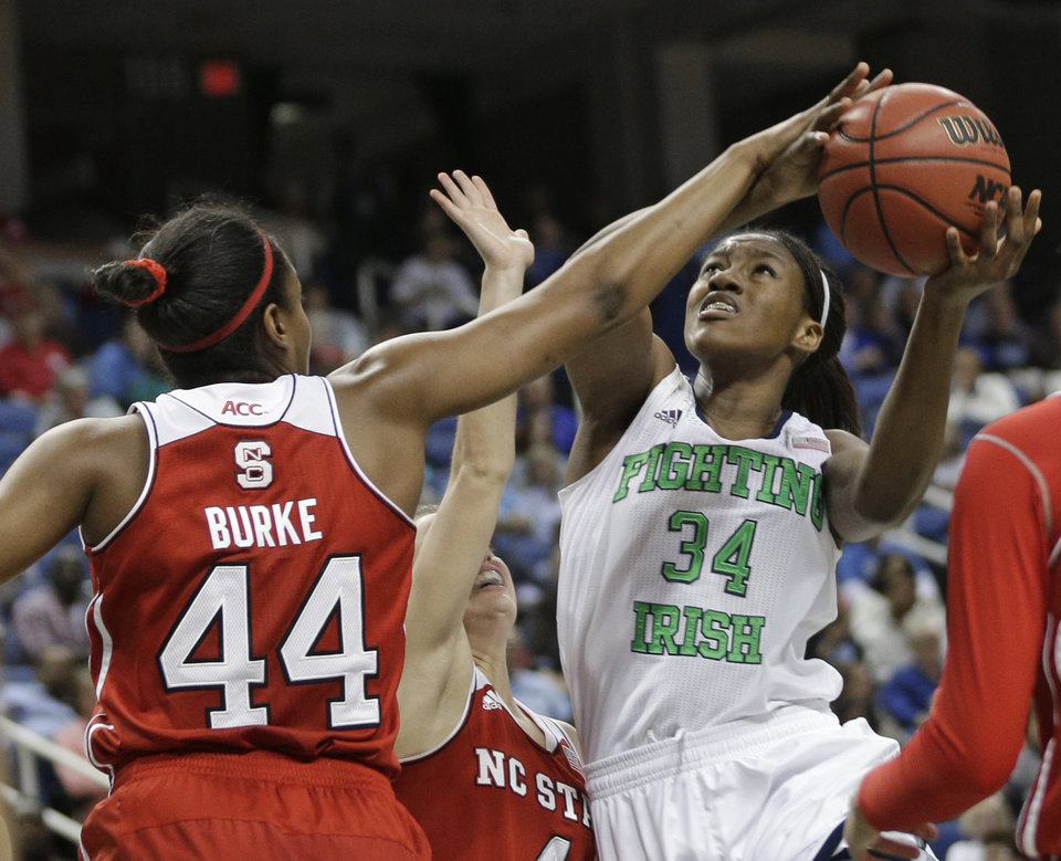 Photo - Notre Dame's Markisha Wright (34) shoots as North Carolina State's Kody Burke (44) defends during the second half of an NCAA college basketball semifinal game at the Atlantic Coast Conference tournament in Greensboro, N.C., Saturday, March 8, 2014. Notre Dame won 83-48. (AP Photo/Chuck Burton)