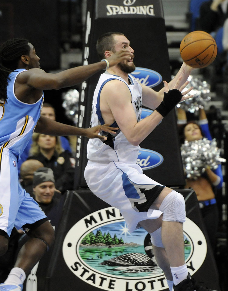 Photo -   Minnesota Timberwolves' Kevin Love, right, receives a pass before being fouled by Denver Nuggets' Kenneth Faried, left, in the second half of an NBA basketball game on Wednesday, Nov. 21, 2012, in Minneapolis. The Nuggets won 101-94. Love led the Timberwolves with 34 points and 14 rebounds while Faried had 14 rebounds for the Nuggets. (AP Photo/Jim Mone)