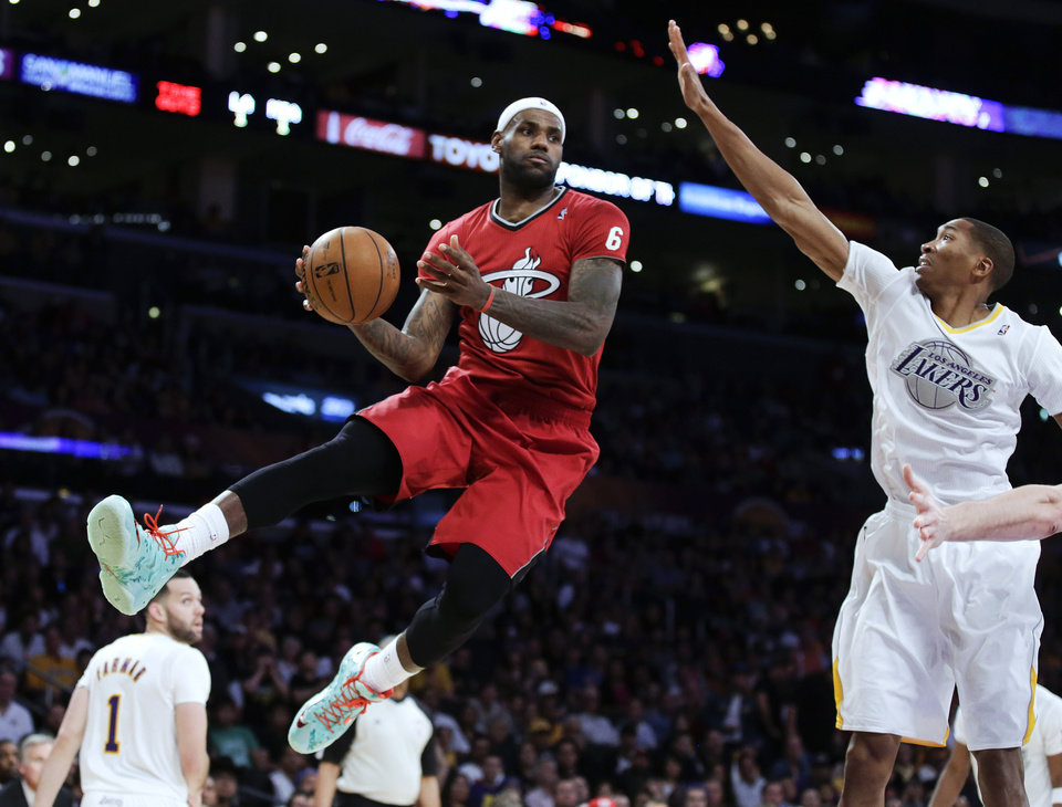 Photo - Miami Heat forward LeBron James, left, passes around Los Angeles Lakers guard Wesley Johnson during the second half of an NBA basketball game in Los Angeles, Wednesday, Dec. 25, 2013. (AP Photo/Chris Carlson)