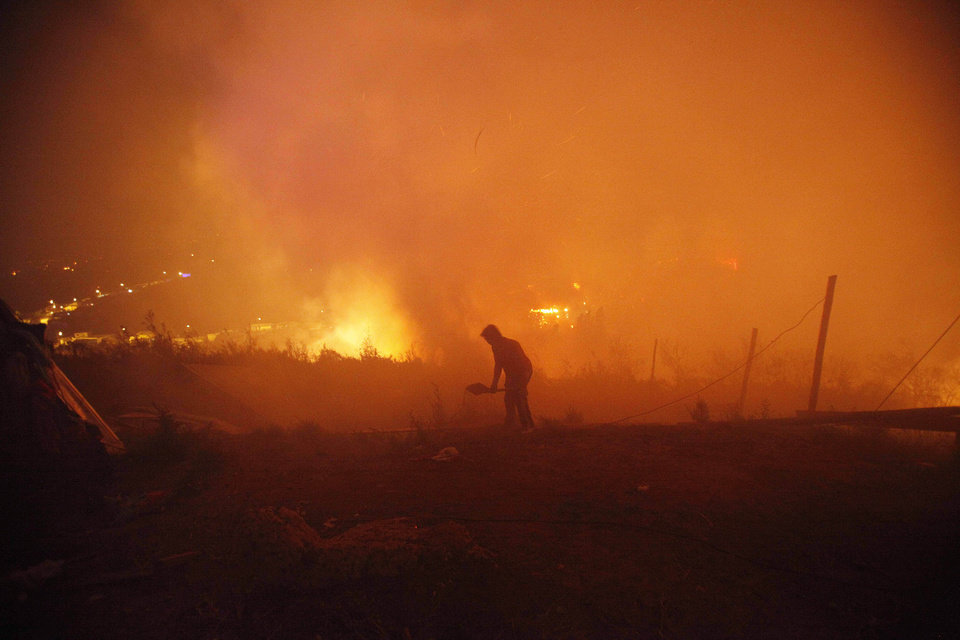Photo - A person helps to extinguish flames as a large forest fire reaches urban areas in Valparaiso, Chile, Sunday April 13, 2014. Authorities say the fires have destroyed hundreds of homes, forced the evacuation of thousands and claimed the lives of at least seven people.  ( AP Photo/ Luis Hidalgo)