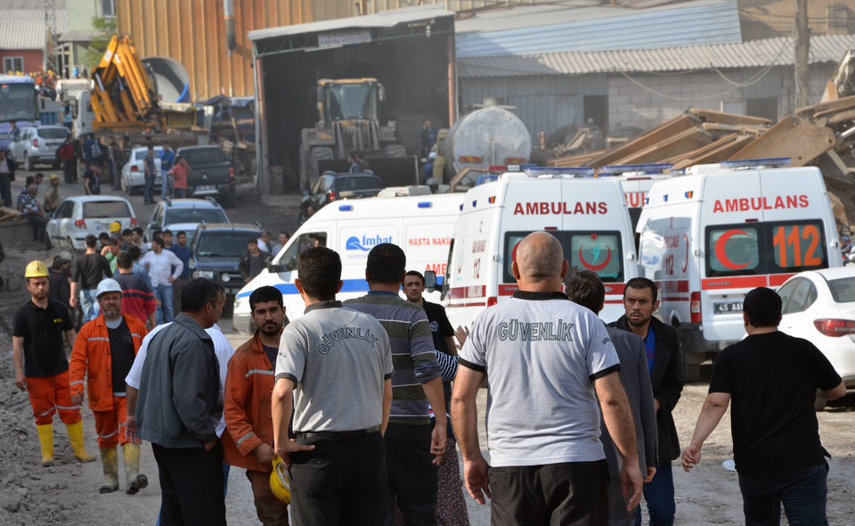 Photo - Rescue workers and ambulances at the entrance of the mine after an explosion and fire at a coal mine in Soma, in western Turkey, Tuesday, May 13, 2014.  An explosion and fire at a coal mine in western Turkey killed at least one miner Tuesday and left up to 300 workers trapped underground, a Turkish official said. Twenty people were rescued from the mine in the town of Soma in Manisa province but one later died in the hospital, Soma administrator Mehmet Bahattin Atci told reporters. The town is 250 kilometers (155 miles) south of Istanbul. (AP Photo/IHA) TURKEY OUT