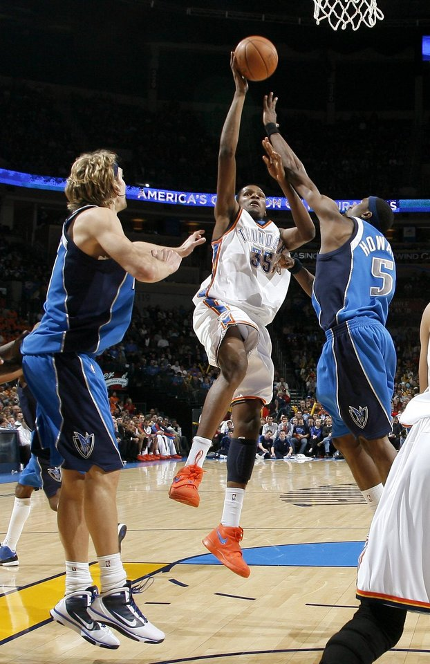 Photo - Oklahoma City's Kevin Durant goes to the basket between Dirk Nowitzki , left, and Josh Howard of Dallas during the NBA basketball game between the Oklahoma City Thunder and the Dallas Mavericks at the Ford Center in Oklahoma City on Wednesday, December 16, 2009. Photo by Bryan Terry, The Oklahoman
