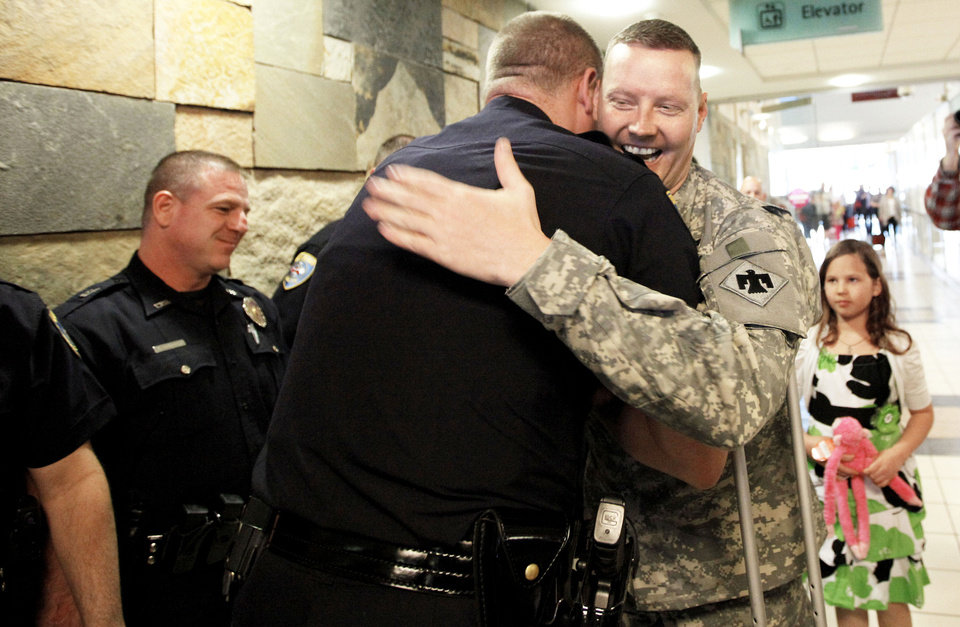 Photo - MILITARY / RETURN: Edmond Police Sgt. Damon Minter, Edmond Police officer Kyle Stoy and Oklahoma National Guard soldier returns home at Will Rogers World Airport in  Oklahoma City, Thursday, March 22, 2012. Photo by Sarah Phipps, The Oklahoman.