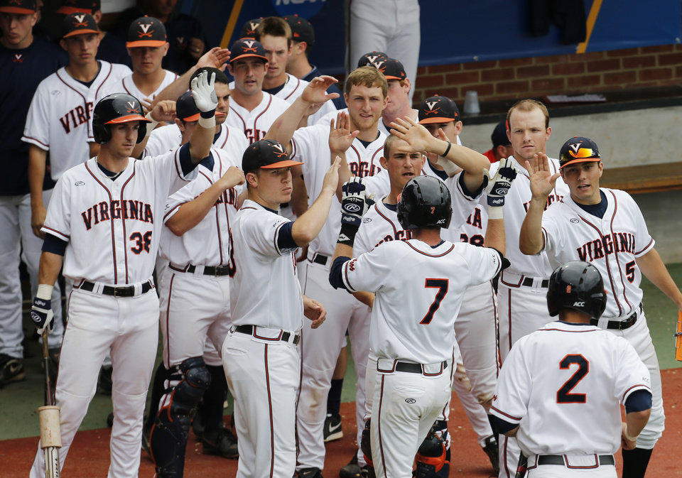 Photo - Virginia infielder Branden Cogswell (7) is welcomed back to the bench in the third inning after a score against Bucknell during an NCAA College regional tournament baseball game in Charlottesville, Va., Friday, May 30, 2014.   (AP Photo/Steve Helber)