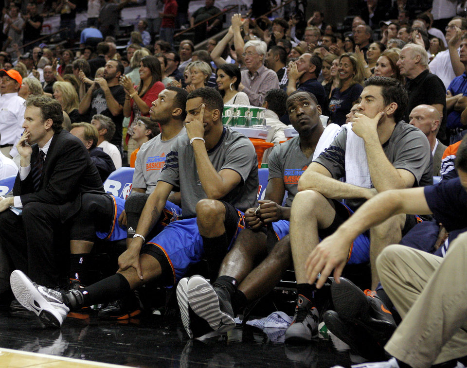 Photo - Oklahoma City's Daequan Cook, left, Thabo Sefolosha, Kendrick Perkins, and Nick Collison sit on the bench as the San Antonio crowd cheers during Game 2 of the Western Conference Finals between the Oklahoma City Thunder and the San Antonio Spurs in the NBA playoffs at the AT&T Center in San Antonio, Texas, Tuesday, May 29, 2012. Oklahoma City lost 120-111. Photo by Bryan Terry, The Oklahoman