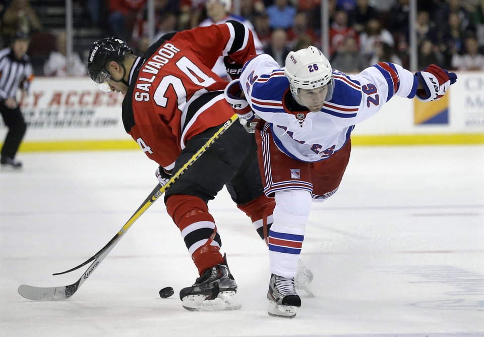 Photo - New Jersey Devils' Bryce Salvador (24) gets tied up with New York Rangers' Martin St. Louis (26) during the first period of an NHL hockey game game Saturday, March 22, 2014, in Newark, N.J. (AP Photo/Mel Evans)