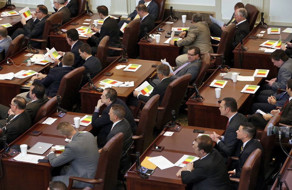 Photo - Lawmakers read over paperwork as Gov. Mary Fallin speaks during the Oklahoma Legislature's 2016 State-of-the-State Address by Gov. Mary Fallin in the chamber of the House of Representatives at the Oklahoma state capitol on Monday, Feb. 1, 2016, in Oklahoma City, Okla. Photo by Jim Beckel, The Oklahoman