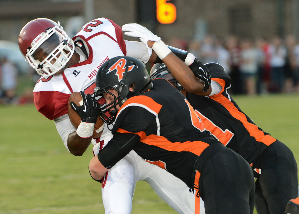 Photo - Muldrow's Dominic Blue, left, is tackled by Roland's Austin Cantrell and Madison Bunch on Thursday, Sept. 5, 2013 at Roland. PHOTO BY BRIAN D. SANDERFORD, TIMES RECORD