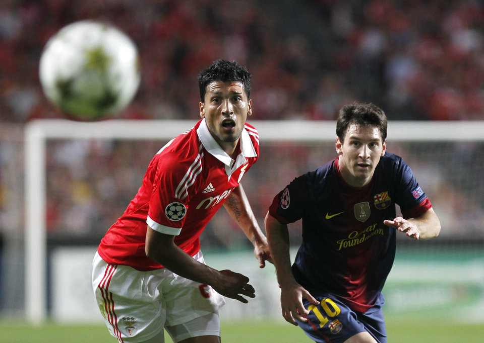 Photo -   Barcelona's Lionel Messi, and Benfica's Ezequiel Garay, both from Argentina, eye the ball during their Champions League group G soccer match at Benfica's Luz stadium in Lisbon, Tuesday, Oct. 2, 2012. Barcelona defeated Benfica 2-0. (AP Photo/Francisco Seco)