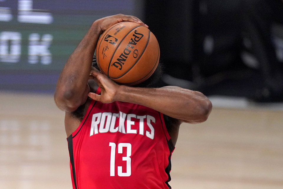 Photo - Houston Rockets' James Harden (13) attempts to maintain control of the ball during the first half of an NBA first-round playoff basketball game against the Oklahoma City Thunder, Monday, Aug. 31, 2020, in Lake Buena Vista, Fla. (AP Photo/Mark J. Terrill)