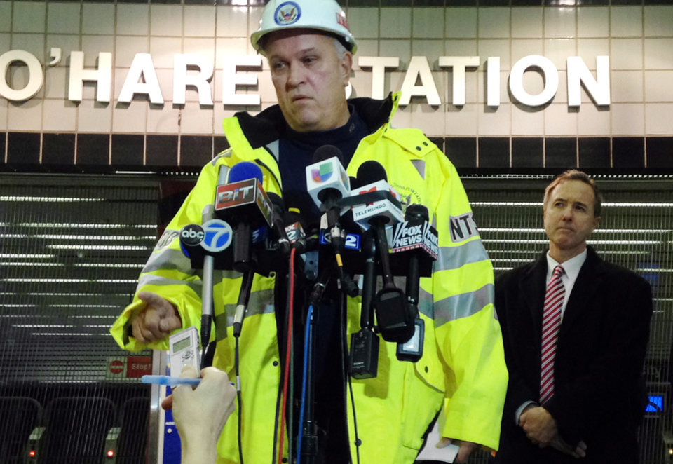 Photo - Tim DePaepe, an investigator with the National Transportation Safety Board, accompanied by Chicago Transit Authority President Forrest Claypool, right, speaks during a news conference Monday, March 24, 2014, at Chicago's O'Hare International Airport in Chicago. The NTSB is leading an investigation into why an eight-car Chicago public-transit train jumped the tracks, skidded across a platform and scaled an escalator that leads to one of the nation's busiest airports early Monday, injuring 32 people. (AP Photo/Carla K. Johnson)