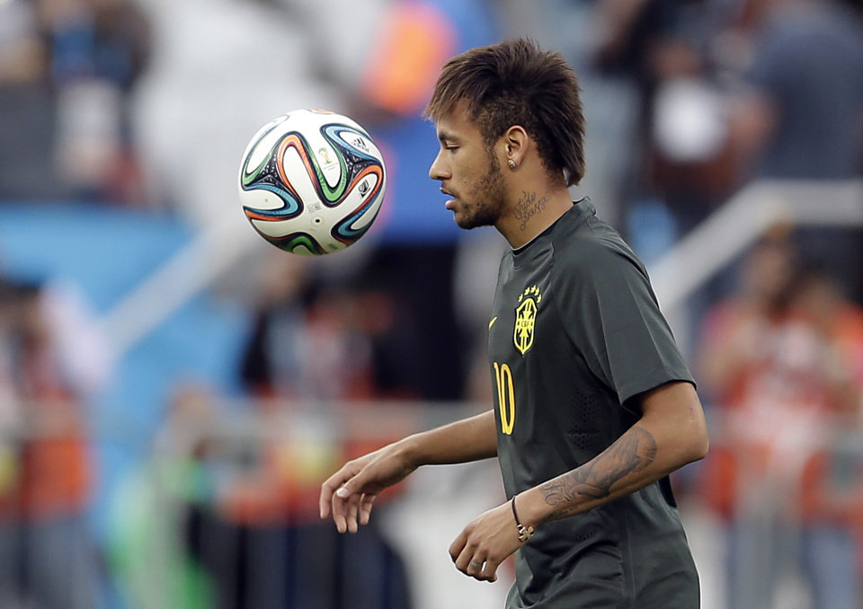 Photo - Brazil's Neymar heads the ball during an official training session the day before the group A World Cup soccer match between Brazil and Croatia in the Itaquerao Stadium, Sao Paulo       , Brazil, Wednesday, June 11, 2014.  (AP Photo/Andre Penner)
