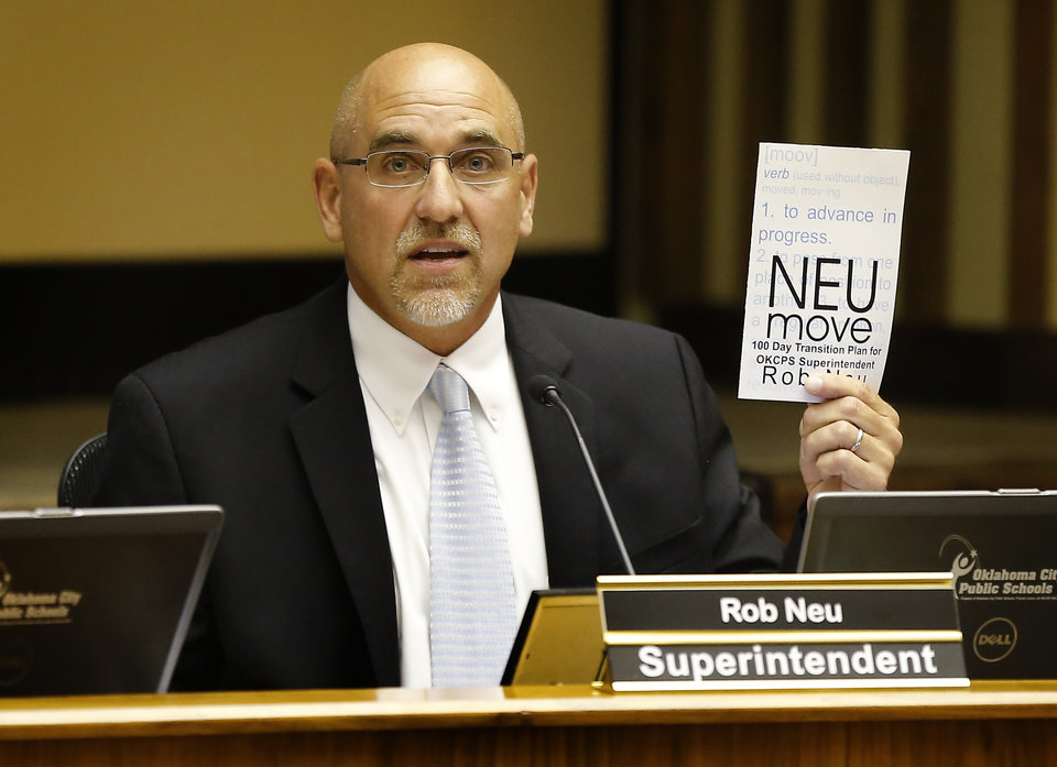 Photo -  New Oklahoma City Public Schools Superintendent Rob Neu holds up a paper that outlines his transition plan during his first school board meeting Tuesday. Photo by Bryan Terry, The Oklahoman   Bryan Terry -  THE OKLAHOMAN