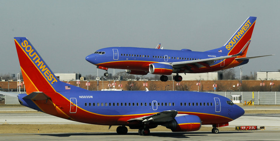 FILE - In this Feb. 9, 2012 file photo, a Southwest Airlines Boeing 737 waits to take off at Chicago's Midway Airport as another lands. Southwest Airlines Co. says fourth-quarter earnings in 2012 fell by nearly half on higher spending for fuel, labor and maintenance. (AP Photo/Charles Rex Arbogast, File)