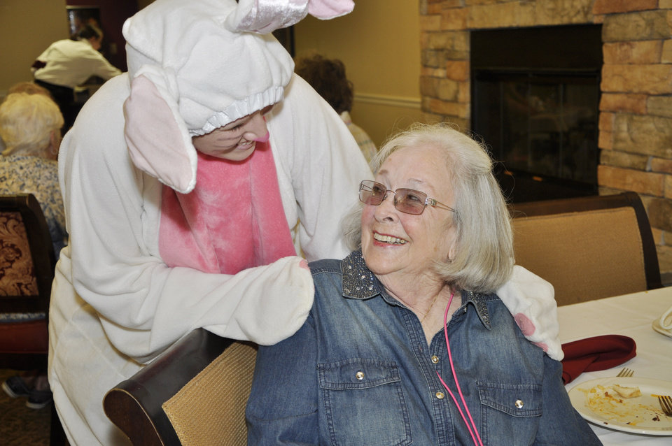 Photo -  The Easter Bunny, portrayed by Morgan Fitzgerald, greets Ann Hodge in the dining room at Touchmark at Coffee Creek in Edmond. Photo by M. Tim Blake, For The Oklahoman   M. Tim Blake