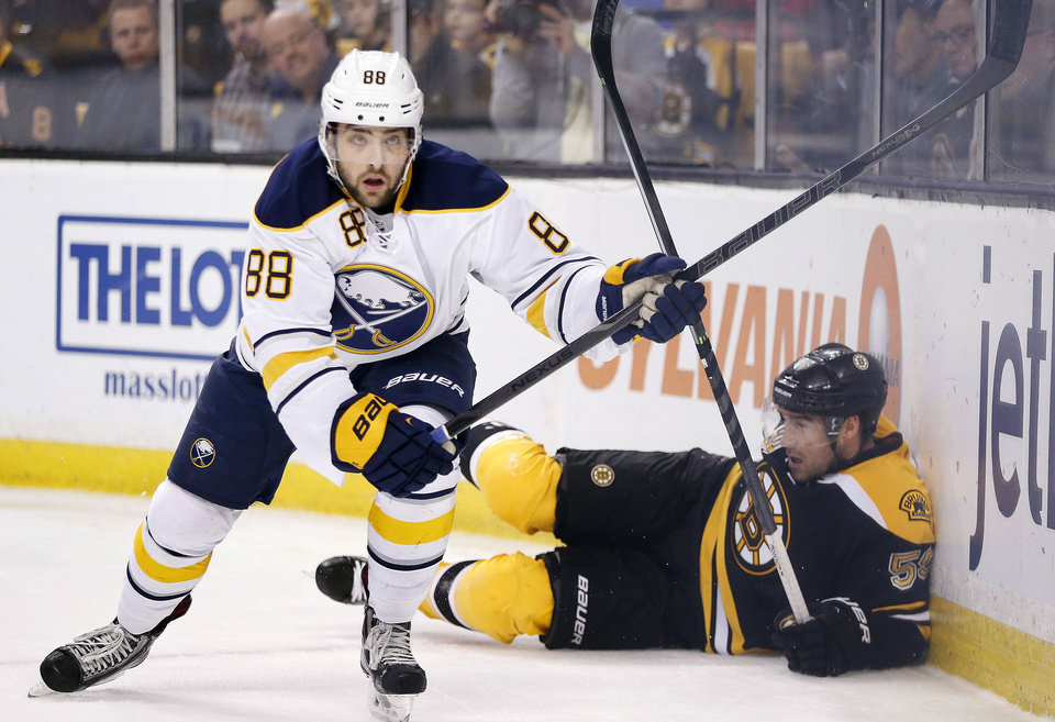 Photo - Buffalo Sabres' Cory Conacher (88) skates away after checking Boston Bruins' Johnny Boychuk (55) into the boards during the first period of an NHL hockey game in Boston, Saturday, April 12, 2014. (AP Photo/Michael Dwyer)