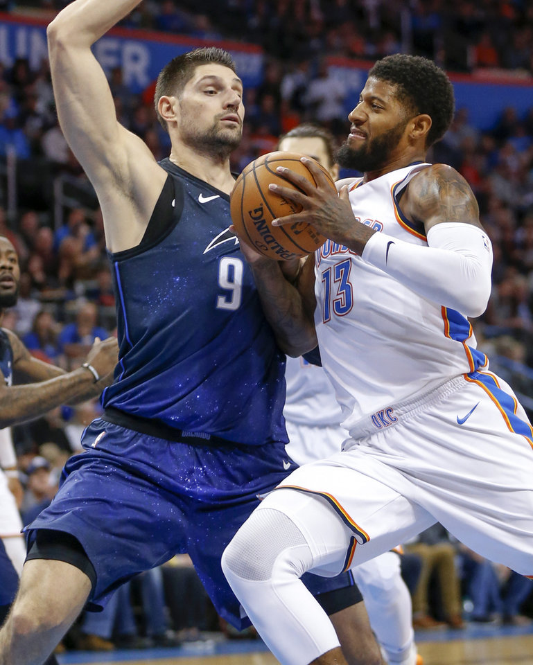 Photo - Oklahoma City's Paul George (13) drives against Orlando's Nikola Vucevic (9) during an NBA basketball game between the Oklahoma City Thunder and the Orlando Magic at Chesapeake Energy Arena in Oklahoma City, Monday, Feb. 26, 2018. Photo by Nate Billings, The Oklahoman