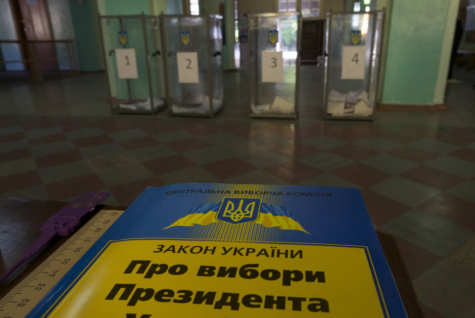 Photo - A book with election law lies on a table at a polling station in Mariupol, Ukraine, on Sunday, May 25, 2014. Ukraine's critical presidential election got underway Sunday under the wary scrutiny of a world eager for stability in a country rocked by a deadly uprising in the east. Book reads