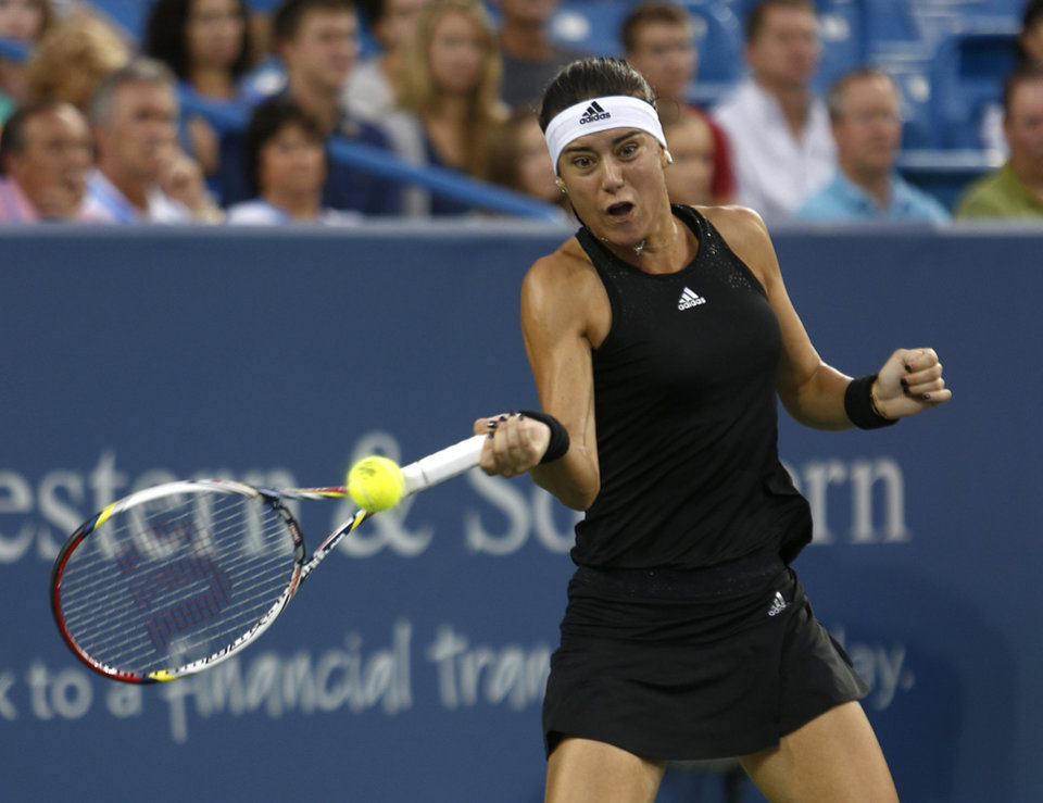 Photo - Sorana Cirstea, from Romania, returns to Ana Ivanovic, from Serbia, in a first round match at the Western & Southern Open tennis tournament, Monday, Aug. 11, 2014, in Mason, Ohio. (AP Photo/David Kohl)