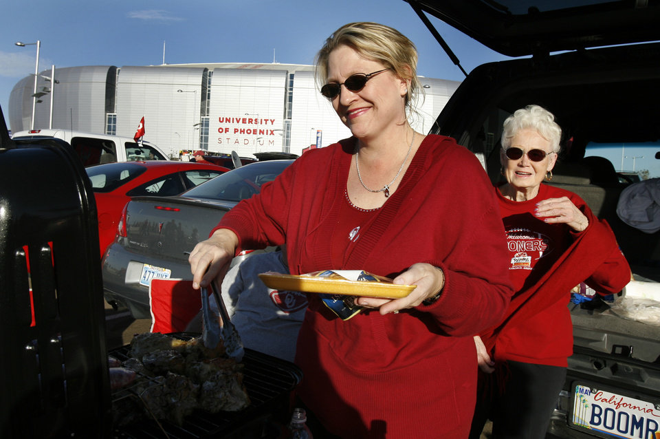 Photo - Andrea Garibay of Lawton and her mother-in-law Jo Garibay of Los Angeles tailgate in the parking lot of the stadium before the Fiesta Bowl college football game between the University of Oklahoma Sooners (OU) and the West Virginia University Mountaineers (WVU) at The University of Phoenix Stadium on Wednesday, Jan. 2, 2008, in Glendale, Ariz. 