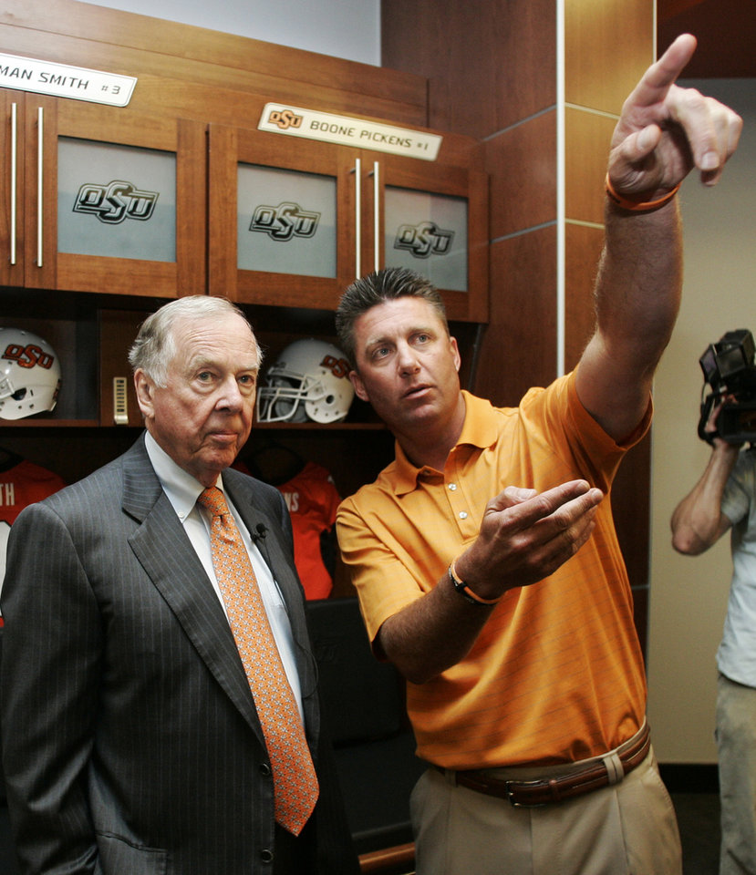 Photo -  Oklahoma State football coach Mike Gundy, right, points out some of the features of the new locker room to T. Boone Pickens, left, while standing in front of a locker reserved for Pickens, Monday, Aug. 17, 2009, in Stillwater, Okla. Through a series of donations, Pickens provided the bulk of the funding for a $286 million stadium overhaul. (AP Photo/Sue Ogrocki)   ORG XMIT: OKSO107