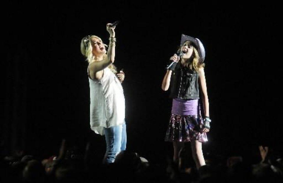"Country music superstar Carrie Underwood sings ""All American Girl"" with Kaitlyn Finn, 10, of Damascus, Ore., at the Bi-Mart Willamette Country Music Festival east of Brownsville, Ore., Friday Aug. 16, 2013. Finn, who suffered from liver cancer and has received a liver transplant, was granted the chance to sing with Underwood through the Make-A-Wish Foundation. (AP)"