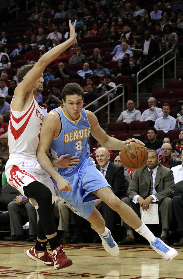 Photo - Denver Nuggets' Danilo Gallinari (8) drives the ball around Houston Rockets' Chandler Parsons, left, in the first half of an NBA basketball game Wednesday, Jan. 23, 2013, in Houston. (AP Photo/Pat Sullivan)