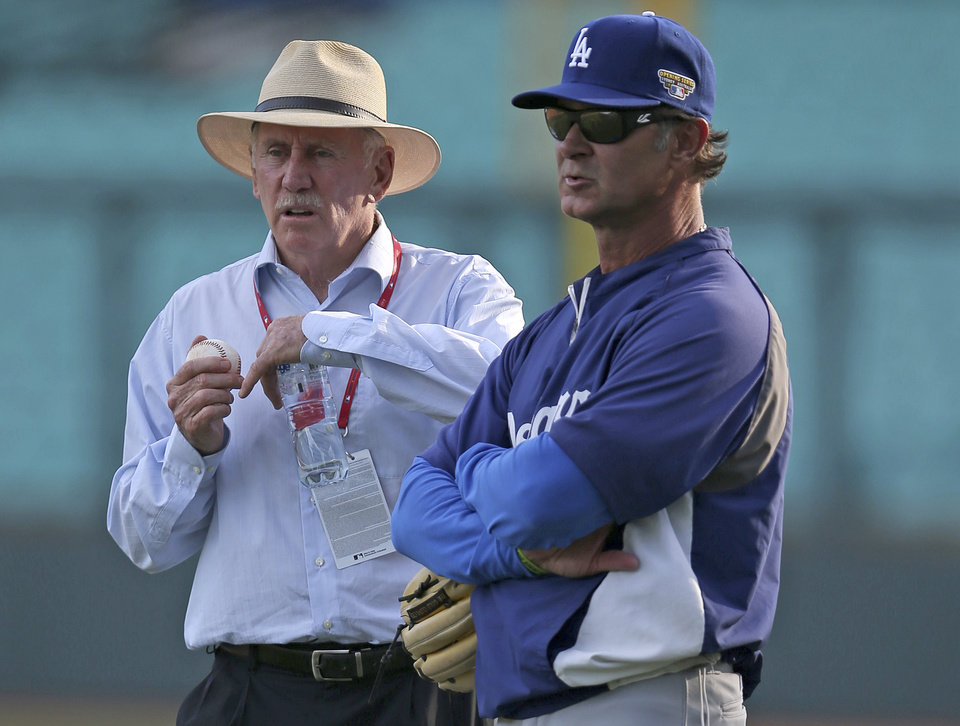 Photo - Los Angeles Dodgers manager Don Mattingly, right, talks with former Australian cricket captain Ian Chappell while the Dodgers train in Sydney, Thursday, March 20, 2014. The Diamondbacks and the Los Angeles Dodgers open the Major League Baseball regular season with games on Saturday and Sunday. (AP Photo/Rick Rycroft)