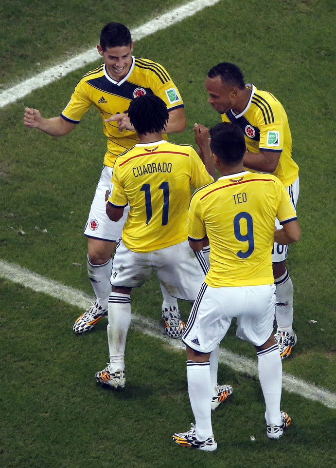 Photo - Colombia's James Rodriguez, left, dances as he celebrates with his teammates after scoring his side's second goal during the World Cup round of 16 soccer match between Colombia and Uruguay at the Maracana Stadium in Rio de Janeiro, Brazil, Saturday, June 28, 2014. (AP Photo/Fabrizio Bensch, Pool)