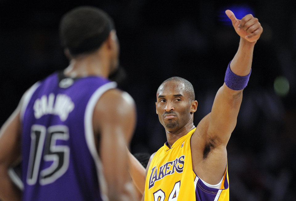 Photo - Los Angeles Lakers guard Kobe Bryant, right, gestures as Sacramento Kings guard John Salmons (15) looks on after their NBA basketball game, Friday, Dec. 12, 2008 in Los Angeles. The Lakers 112-103.  (AP Photo/Mark J. Terrill) ORG XMIT: LAS107