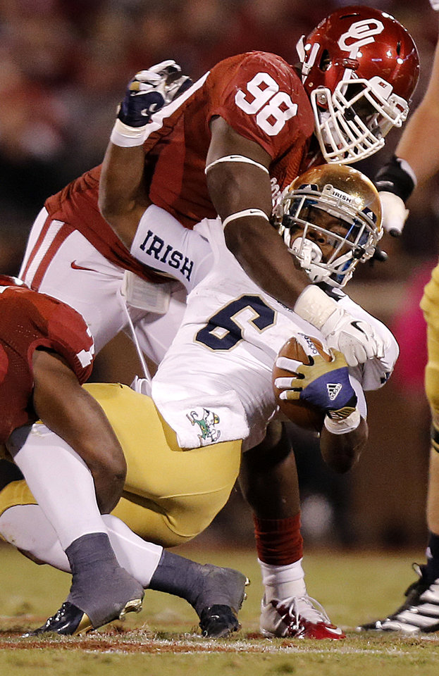 OU\'s Chuka Ndulue (98) brings down Notre Dame \'s Theo Riddick (6) during the college football game between the University of Oklahoma Sooners (OU) and the Notre Dame Fighting Irish at the Gaylord Family-Oklahoma Memorial Stadium on Saturday, Oct. 27, 2012, in Norman, Okla. Photo by Chris Landsberger, The Oklahoman