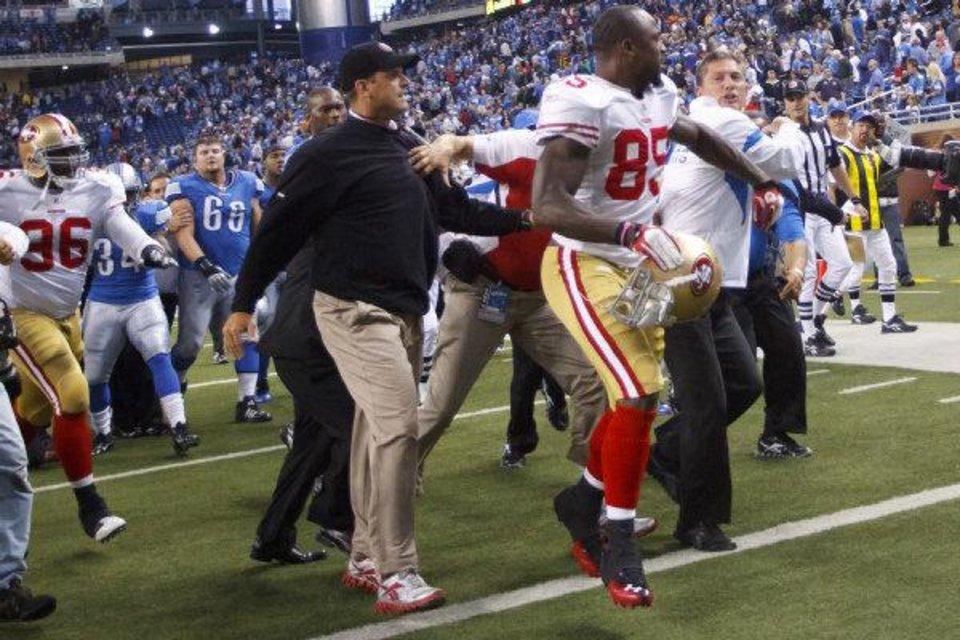 Photo - This Oct. 16, 2011 photo shows San Francisco 49ers' Venron Davis (85), between 49ers coach Jim Harbaugh, left, and Detroit coach Jim Schwartz, after an NFL football game, in Detroit. After the 49ers knocked Detroit from the unbeaten ranks 25-19 in a game that matched the pregame hype, both coaches bumped each other in an emotionally charged exchange. (AP Photo/Rick Osentoski, File)  Rick Osentoski