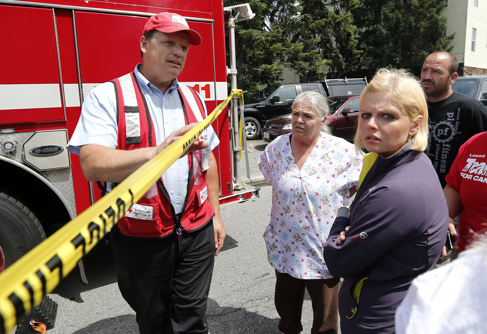 Photo - People seek information about their loved ones from a member of the Red Cross, left,  as they stand outside a burned three-story apartment and business building in Lowell, Mass., Thursday, July 10, 2014, where officials said seven people died in a fast-moving pre-dawn fire.   The cause and origin of the blaze remain under investigation, State Fire Marshal Stephen Coan said. (AP Photo/Elise Amendola)