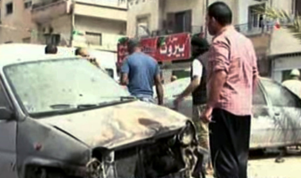 Photo - In this image made from video provided by APTN, Libyan men look at a damaged car at the site of a car bomb explosion in Benghazi, Libya, Monday, May 13, 2013. A car bomb exploded Monday near a hospital in the eastern Libyan city of Benghazi, killing many, officials said, in one of the biggest attacks since the end of the civil war that ousted former dictator Moammar Gadhafi. (AP Photo/APTN, Al Ahrar)