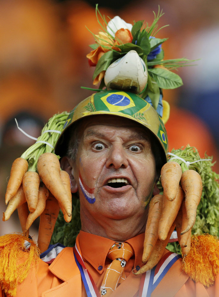 Photo - In this Friday, June 13, 2014 photo, a Dutch fan wears a homemade hat during the group B World Cup soccer match between Spain and the Netherlands at the Arena Ponte Nova in Salvador, Brazil. A dominating second half had the orange-clad Dutch fans in Arena Fonte Nova on their feet as they watched their team thrash the world champions 5-1. It was the worst loss for Spain in the game's showcase tournament since a 6-1 defeat to Brazil in 1950. (AP Photo/Natacha Pisarenko)