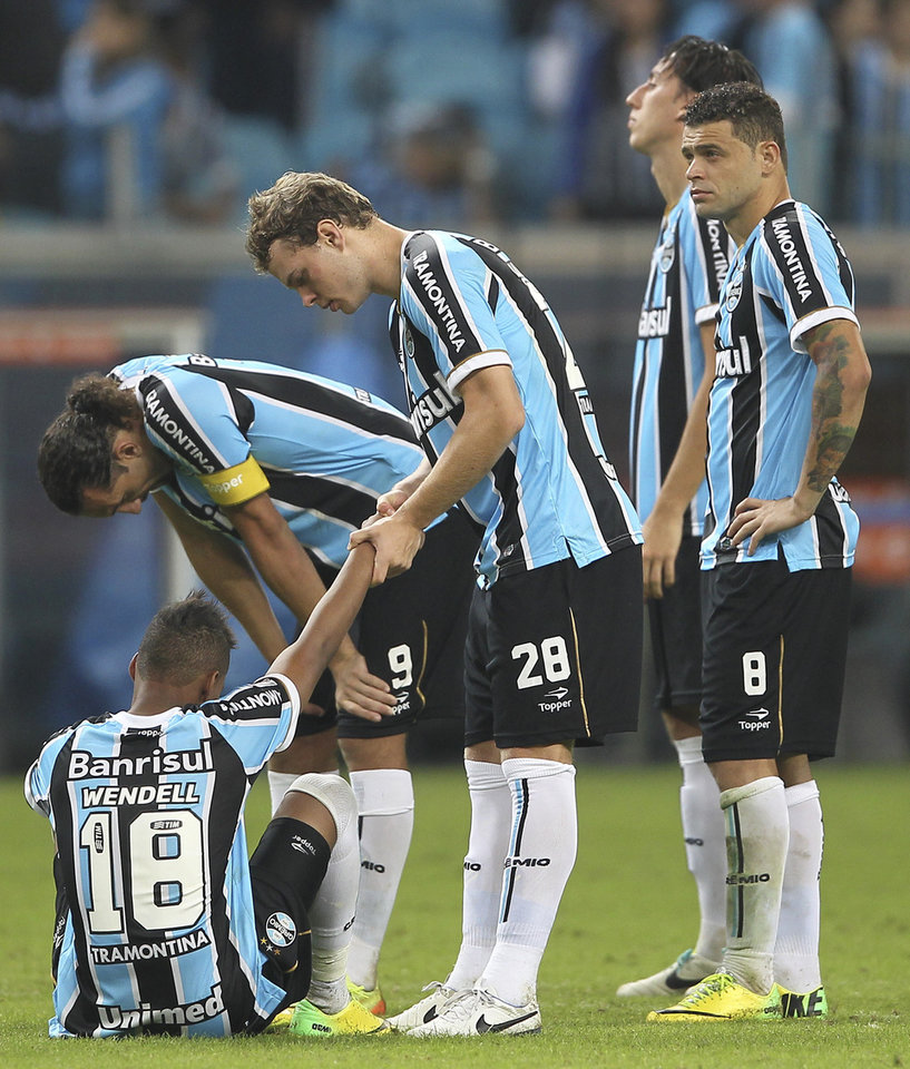 Photo - Brazil's Gremio players, from left, Wndell, Hernan Barcos, Lucas, and Edinho react after being defeated in penalties by Argentina's San Lorenzo during a Copa Libertadores soccer match in Porto Alegre, Brazil, Wednesday, April 30, 2014. San Lorenzo defeated Gremio in a penalty shootout. (AP Photo/Nabor Goulart)