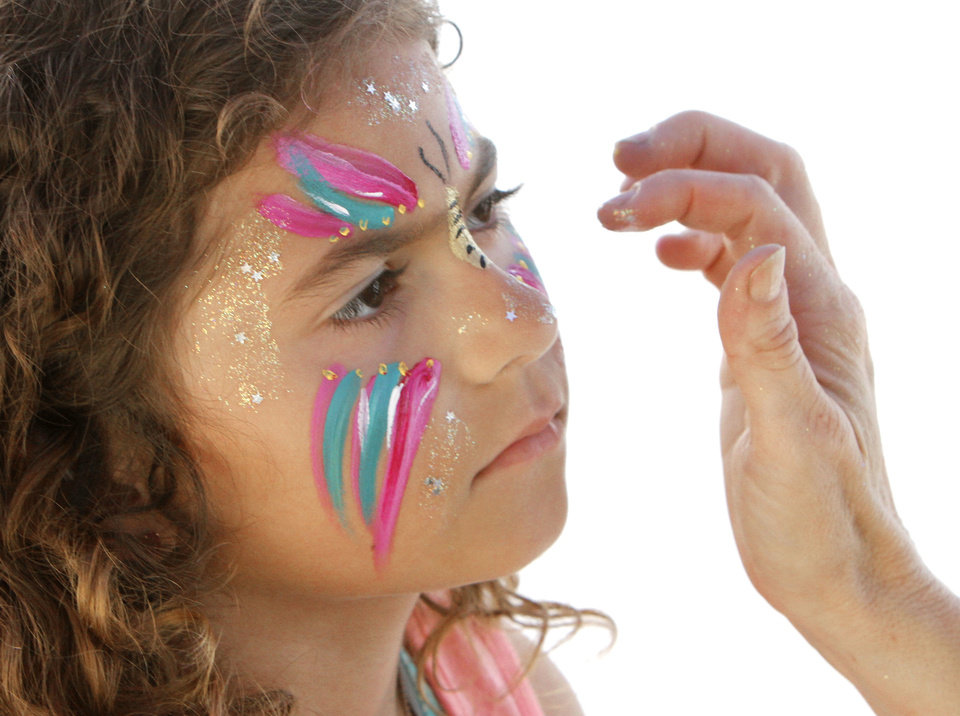 Photo - Seven year old Heaven Autrey has her face painted by Clarissa Sharp, with
