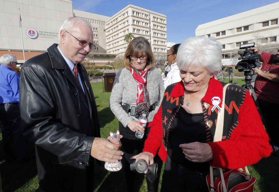 Photo - Tucson shooting survivors Bill Posey and Nancy Bowman, center, and Patricia Maisch, who helped stop the shooter, ring bells during a remembrance ceremony on the third anniversary of the Tucson shootings, Wednesday, Jan. 8, 2014, in Tucson, Ariz. Six people were killed and 13 wounded, including U.S. Rep. Gabrielle Giffords, D-Ariz., in the shooting rampage at a community event hosted by Giffords in 2011.  Jared Lee Loughner was sentenced in November 2012 to seven consecutive life sentences, plus 140 years, after he pleaded guilty to 19 federal charges in the shooting. (AP Photo/Matt York)