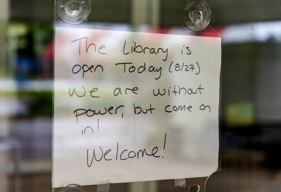 Photo - A sign welcoming people in to the Del City Library after storms knocked out power in Del City, Okla. on Tuesday, Aug. 27, 2019.   [Chris Landsberger/The Oklahoman]