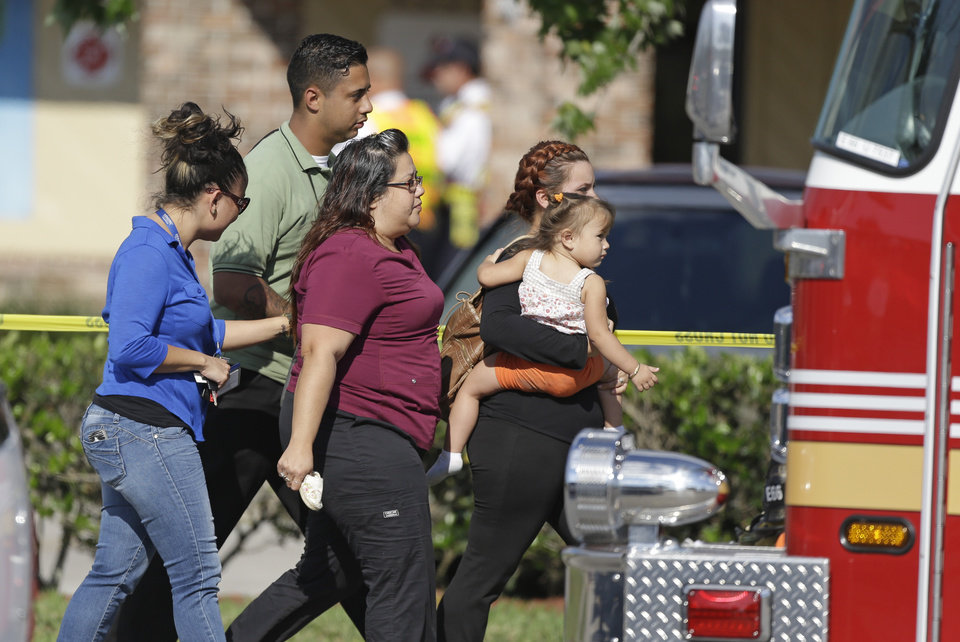 Photo - Parents and relatives leave a day care center with their children after a vehicle crashed into the center, Wednesday, April 9, 2014, in Winter Park, Fla. At least 15 people were injured, including children. (AP Photo/John Raoux)
