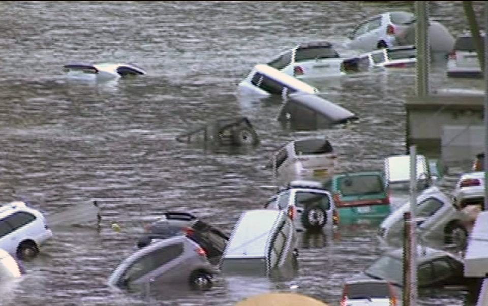 Photo - In this image made off Japan's NHK TV video footage, vehicles are washed away by tsunami in coastal area in eastern Japan after Japan was struck by a magnitude 8.9 earthquake off its northeastern coast Friday, March 11, 2011. (AP Photo/NHK TV) MANDATORY CREDIT, JAPAN OUT, TV OUT, ONLINE OUT, NO SALES, EDITORIAL USE ONLY ORG XMIT: TOK805