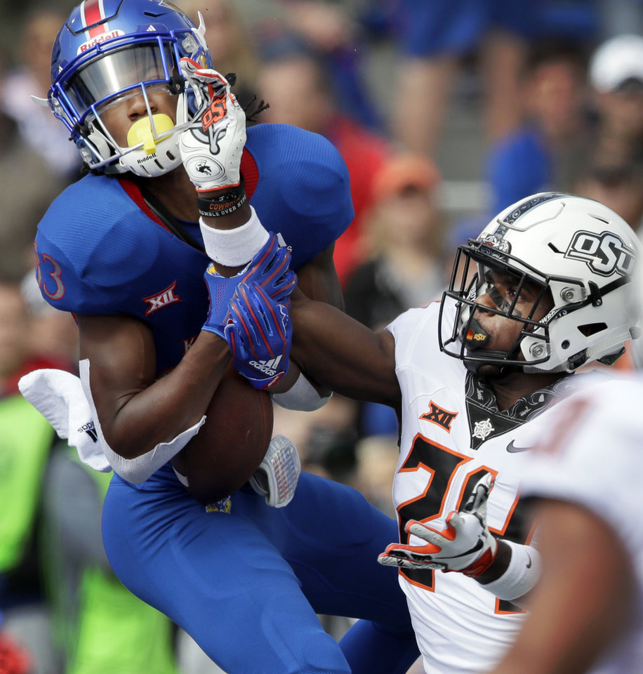 Photo - Kansas wide receiver Kwamie Lassiter II (83) catches a touchdown pass while covered by Oklahoma State safety Jarrick Bernard (24) during the first half of an NCAA college football game in Lawrence, Kan., Saturday, Sept. 29, 2018. (AP Photo/Orlin Wagner)