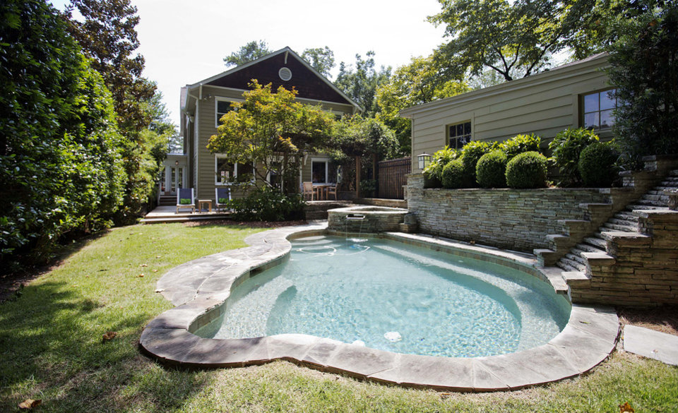 Photo - This is an exterior view of the backyard patio and pool area of a three bedroom house listed for sale at $1,095,000 on Wednesday, July 30, 2014, in the Sherwood Forest neighborhood of Atlanta. The 2,551-square-foot house has two and a half bathrooms and features a detached garage. (AP Photo/David Goldman)