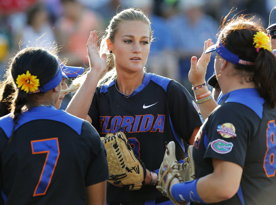 Photo - Florida pitcher Hannah Rogers (13) celebrates with teammates, including Kelsey Stewart (7) and Bailey Castro, between innings during Game 5 of the Women's College World Series softball tournament between Florida and Oregon at ASA Hall of Fame Stadium in Oklahoma City, Friday, May 30, 2014. Photo by Nate Billings, The Oklahoman