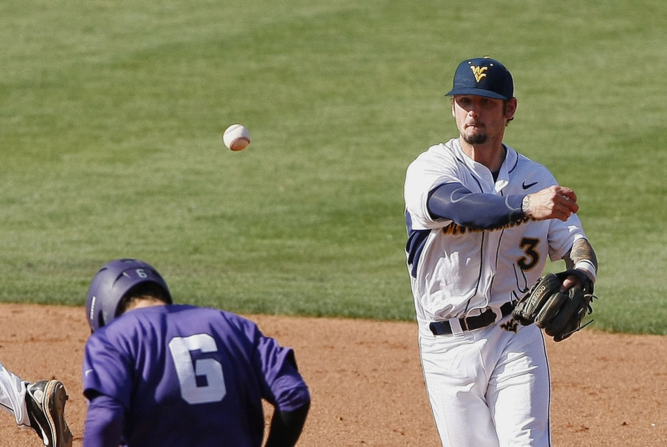 Photo - West Virginia shortstop Taylor Munden throws to first as TCU's Kyle Bacak runs to second in the fifth inning of a second-round game of the Big 12 conference NCAA college baseball tournament in Oklahoma City, Thursday, May 22, 2014. TCU won 6-2. (AP Photo/Alonzo Adams)